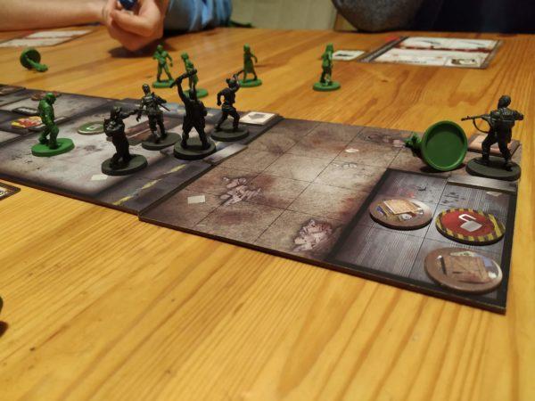 Tous les survivants dans une même salle, sauf Laura, encore au début un zombie à terre