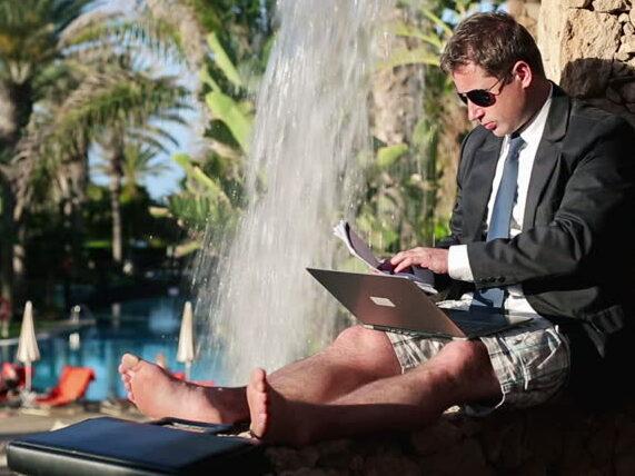 Business man en costard cravate, pc portable sur les genoux, en short et paysage de vacances.